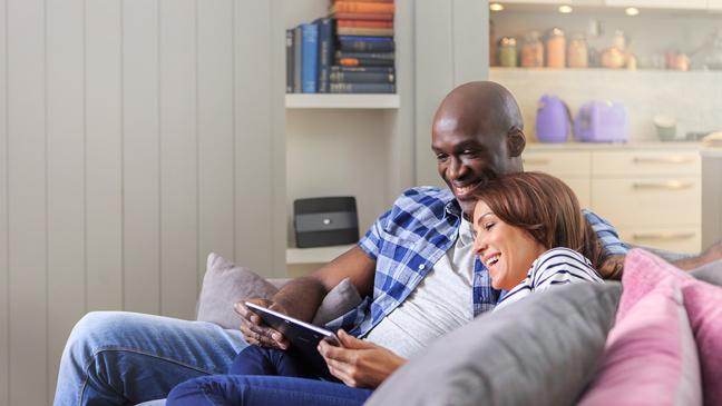 Man and woman on sofa with BT Smart Hub in background