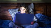 Girl using laptop in bed