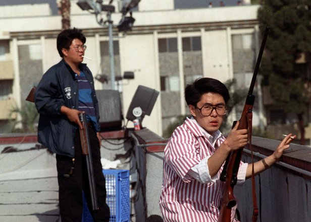 Two Korean men stand on the roof of a grocery store with rifles to prevent looters from entering the store.