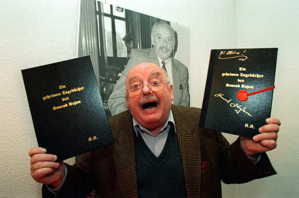 Forger Konrad Kujau, pictured in 1996 with copies of his own book about the event.