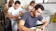 Man at desk writing exam or quiz