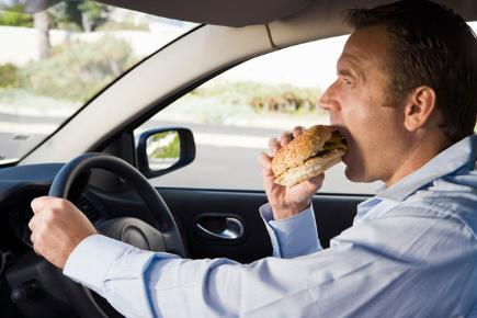 Man eating in car stock image