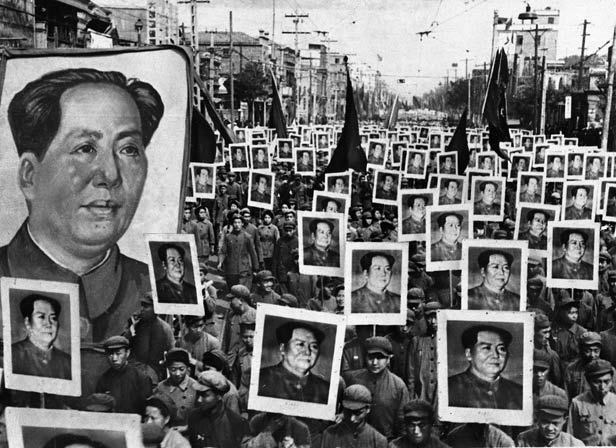 Crowds holding posters of Mao Tse-tung fill the street of a city in China in June 1949, celebrating the triumph of the Communist revolution.