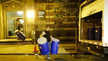 Workers from BioRecovery Corporation carry barrels from Ebola patient Dr Craig Spencer's apartment building in Harlem, New York  (AP)