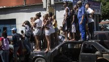 Residents watch as police remove five bodies from a car in Rio de Janeiro. (AP)