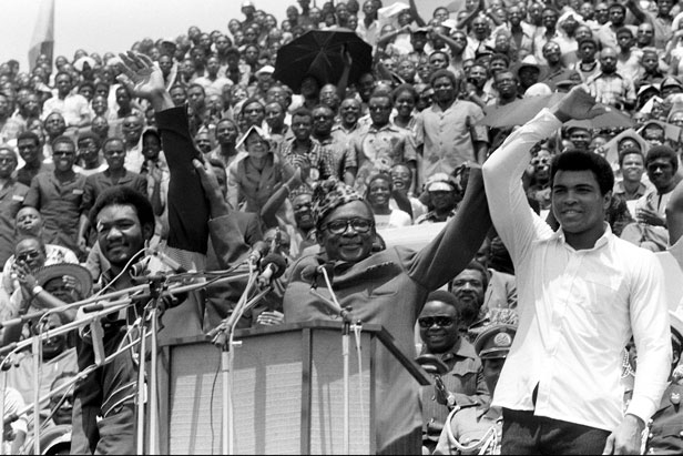 Zaire president Mobutu Sese Seko raises the arms of George Foreman (left) and Muhammad Ali (right) ahead of the fight.