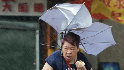 A woman struggles with her umbrella against powerful gusts of wind generated by typhoon Megi in Taipei (AP)