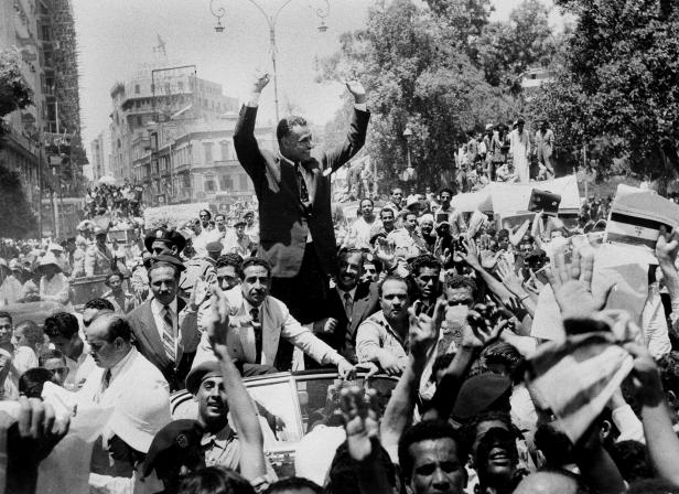 Egypt's President Gamal Abdel Nasser waves to wildly cheering countrymen in Cairo after he announced he would nationalise the Suez Canal.
