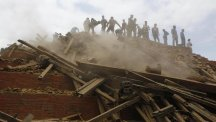 Volunteers help remove debris from a collapsed building in Durbar Square, Kathmandu (AP)