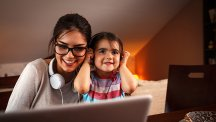 A mother and child use a laptop at home with BT Broadband wi-fi