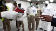 A Nigerian health official uses a thermometer on a worker at the arrivals hall of Murtala Muhammed International Airport in Lagos (AP)