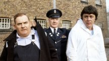 Old lag Fletcher (Ronnie Barker, ledt), fellow prisoner Godber (Richard Beckinsale, right) and prison officer Mackay (Fulton Mackay, centre) during location shooting of Porridge at Chelmsford Jail