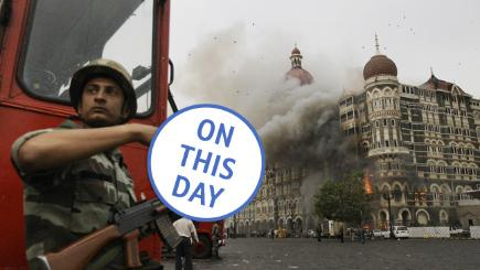 An Indian soldier takes cover as the Taj Mahal hotel burns during gun battle between Indian military and militants.