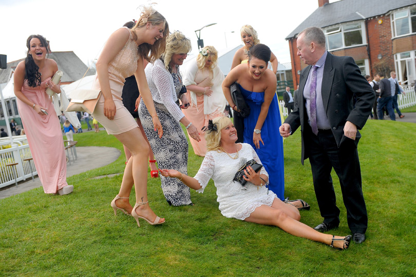 One racegoers heels fail her as she slips on the grass in her white lace dress.