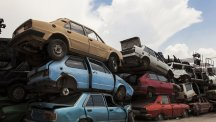 Stock image of old cars piled up in a scrapyard.