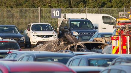 The scene of the crash where four people died after a private jet crash-landed in a car auction site and burst into flames in Hampshire