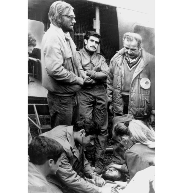 Nando Parrado, glasses at left, stands by as Chilean Air Force medic examine his companion Roberto Canessa on the ground near a rescue helicopter.