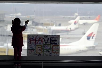 A girl stands next to a sign saying made and written by the public at Kuala Lumpur International Airport in Sepang, Malaysia (AP)