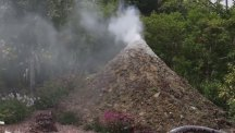 Pensioners build a replica volcano in their back garden which 'erupts' with plumes of smoke