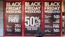 People walk past posters advertising 'Black Friday' sales on Oxford Street, London