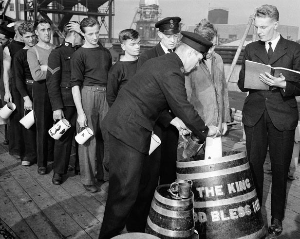 Sailors aboard the British cruiser HMS Phoebe line up for their daily rum issue in December 1941.