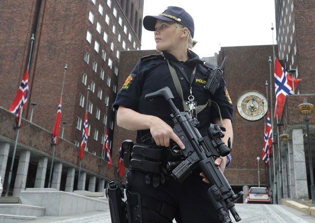 An armed police officer stands in front of the town hall of Oslo following the explosion.