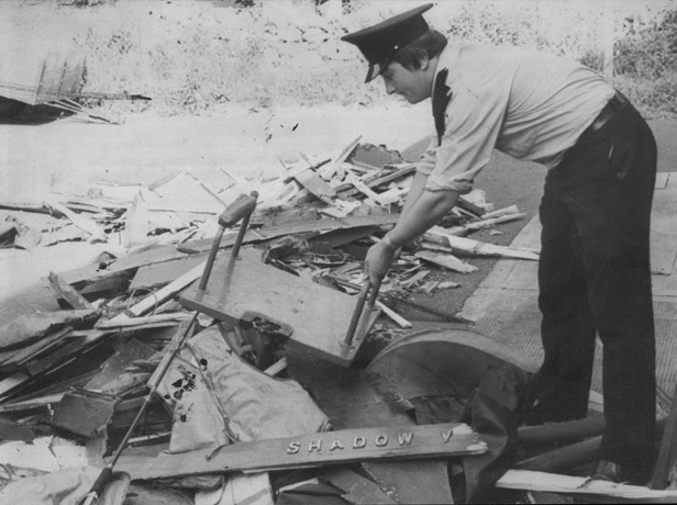 A police officer sorts through wreckage of the boat, Shadow V.