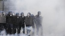 Riot police officers take position amid tear gas smoke in Paris (AP)