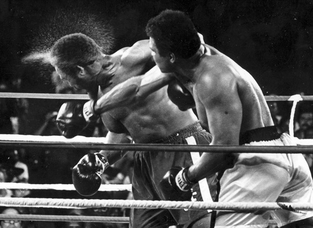 Muhammad Ali catches George Foreman with a right-hander in the seventh round of their fight.