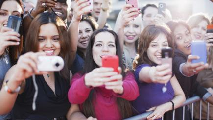 Group of girls holding up phones behind barrier