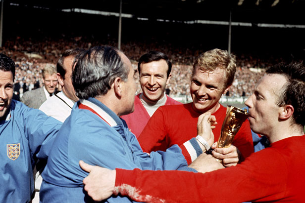 Bobby Moore hands the trophy to manager Alf Ramsey (in blue).