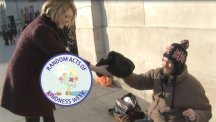 Reporter Becky Barnes hands warm clothes to a homeless man