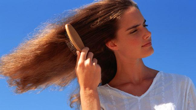 8 reasons for hair loss in women bt woman brushing hair in sunshine pmusecretfo Choice Image