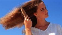 Woman brushing hair in sunshine