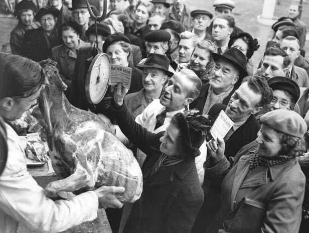 A butcher shows off unrationed reindeer meat at Smithfield Market in 1951.