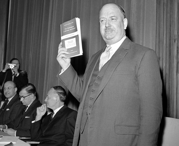 Dr Richard Beeching holds aloft a copy of the pamphlet The Reshaping of British Railways.