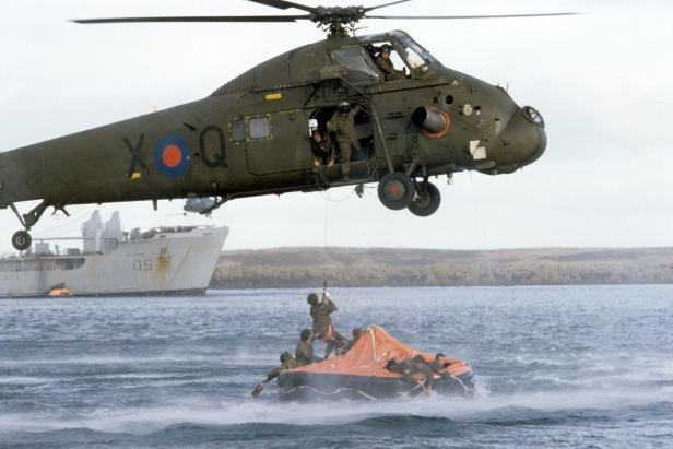 Rescue operations in full swing for the wounded of the Sir Galahad (background, left). A helicopter winches a man up from a life raft.