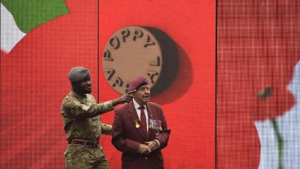 World War II veteran Geoffrey Pattinson, 92, stands with former RAF medic Ben Poku, 34, as they view a video installation unveiled by the Royal British Legion's Poppy Appeal in London