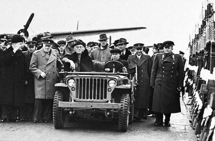 Riding in a US Army jeep, Franklin D Roosevelt is greeted at the airport in Yalta by a Russia guard of honour. Other in attendance include Winston Churchill (beside the jeep) and Russian foreign secretary Vyacheslov Molotov (arm raised)