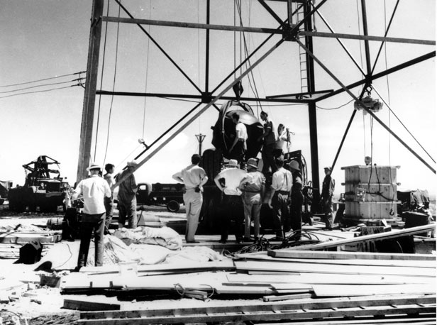 Scientists and workmen rig the bomb to raise it up into a 100-foot tower at the Trinity bomb test site.