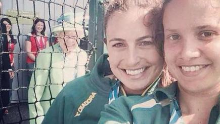 Australian hockey players Jayde Taylor, centre, and Brooke Peris, right, get photo bombed by the Queen