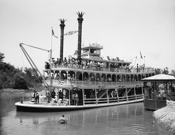 Visitors take a scenic tour of Disneyland on an old river boat.