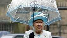 The Queen holds an umbrella as she stands in the rain during her visit to Lancaster Castle, after arriving at the historic city by royal train. (PA)