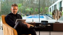 Ryan Reynolds sitting on sofa next to BT Smart Hub