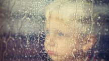 Child looking out of rain window