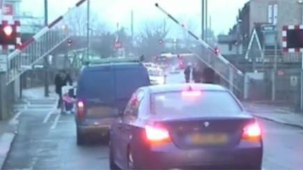Screengrab of a video showing a man pushing a pram ducking under a level crossing barrier.
