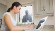 Woman on laptop with burglar in background