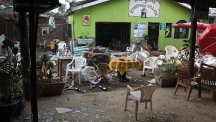 Damaged chairs and tables lie amongst the debris strewn after a bomb attack outside the Ethiopian Village restaurant in Kampala, Uganda (AP)