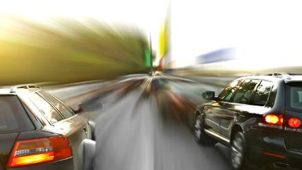 Stock image of two cars side by side on dual carriageway with a blurred background.