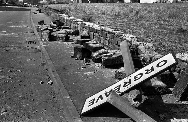 A twisted sign, felled concrete posts and a broken wall tell the story of violence outside the coking plant in Orgreave, South Yorkshire.